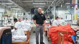 Man standing between working inmates at sewing shop