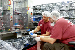 Offenders inspecting juice pouches at the beverage processing plant.