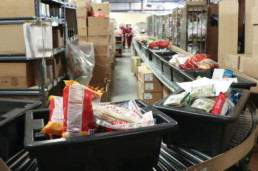 Commissary items moving on conveyor belt to be bagged by inmates
