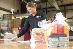 Commissary program manager helping bag commissary items