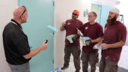 Inmates learning from construction program manager on how to properly use roller to paint walls