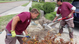 Inmates shoveling dirt to fill hole