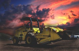 Heavy machinery at open field during sunset.