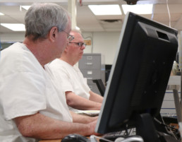 Inmate teaching another inmate on the computer