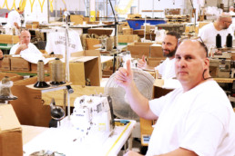 Inmates giving thumbs up while working at the sewing shop in Gunnison Utah