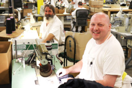 Inmates smiling while working at the sewing shop in Gunnison Utah