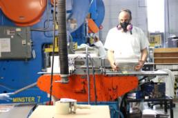 inmates by conveyor belt ensuring license plates meet quality standards