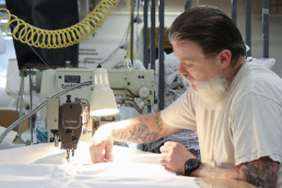 Inmate sewing textiles with sewing machine