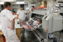 Inmates printing a large banner with large machine