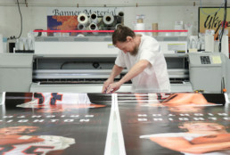 Inmate working on large poster print at the print shop