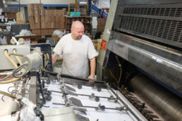 Inmate working large print machine at the print shop