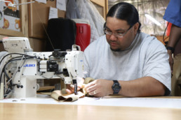 Inmate sewing textiles together
