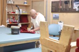 Inmate using staple gun to upholster head rest