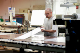 Inmate inspecting sheet of metal