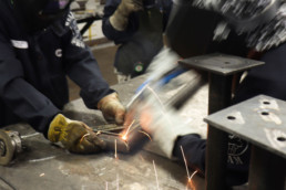 Inmates operating welding equipment to weld metal together