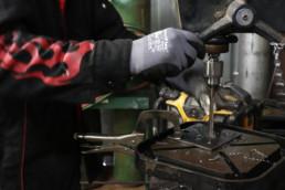 Inmate drilling holes in sheet of metal