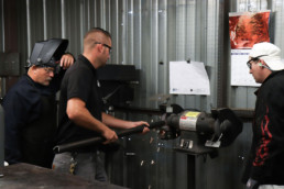 Program supervisor teaching inmates about grinding metal