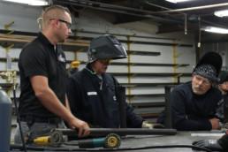 Program supervisor teaching inmates about welding
