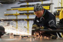 Inmate grinding a piece of metal