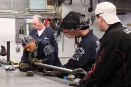 Inmates measuring and doing quality control on metal rail