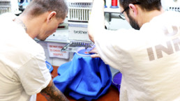 Inmate showing another inmate how to embroider a shirt