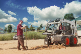 Inmates operating heavy machinery to dig hole to install volleybal post