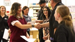 Makin it work graduate receiving her certification and shaking hands with UCI staff